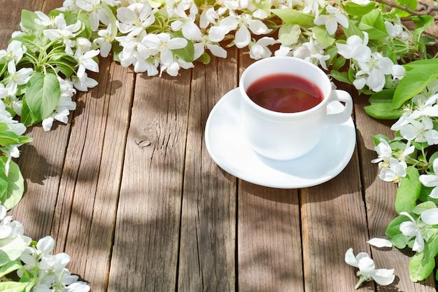 Tasse de thé parmi des fleurs de pommier