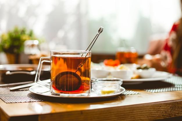 Tasse de thé avec passoire à thé à l'intérieur de la confiture de citron dans la vue latérale de la soucoupe