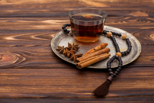 Tasse à thé avec perles de cannelle et chapelet sur assiette