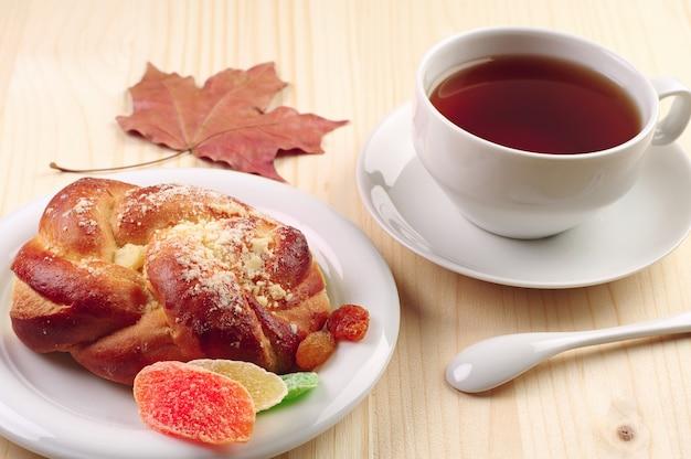 Tasse de thé et petit pain aux fruits secs sur table en bois