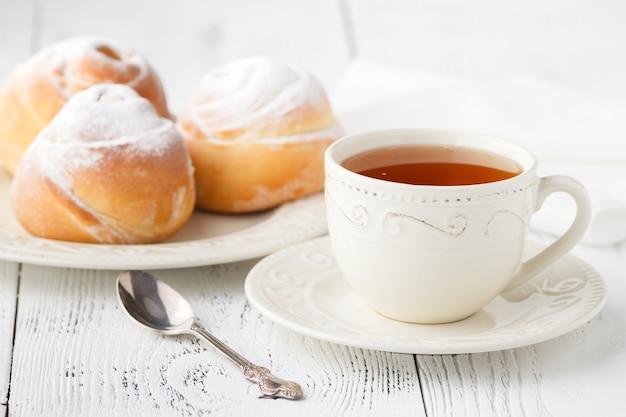Tasse de thé et petites tartes en forme de roses de pomme. tarte aux desserts aux pommes sucrées