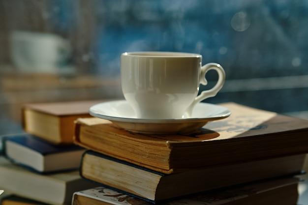 Tasse de thé, une pile de livres sur la fenêtre