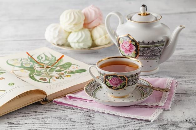 Avec une tasse de thé sur une pile de livres