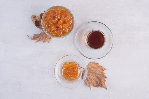 Une tasse de thé avec plaque de verre de confiture sur une surface blanche