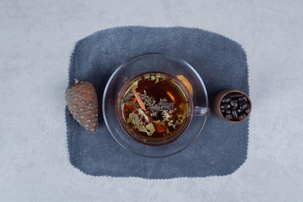 Tasse de thé, pomme de pin et grains sur fond de marbre. photo de haute qualité