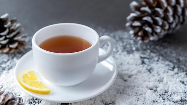 Tasse de thé et pommes de pin.