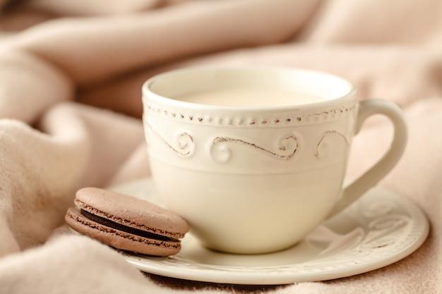 Tasse de thé en porcelaine avec du lait sur fond de laine blanche