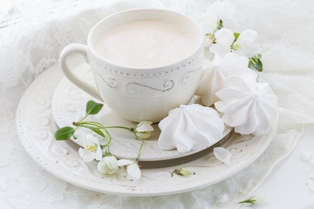 Tasse de thé en porcelaine avec du lait sur le mur blanc