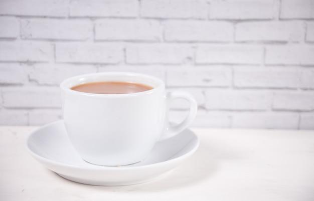 Tasse de thé en porcelaine avec du lait sur le tableau blanc.