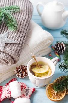 Une tasse de thé pour la nouvelle année. un plaid confortable, une écharpe tricotée et du thé chaud sur un fond en bois bleu