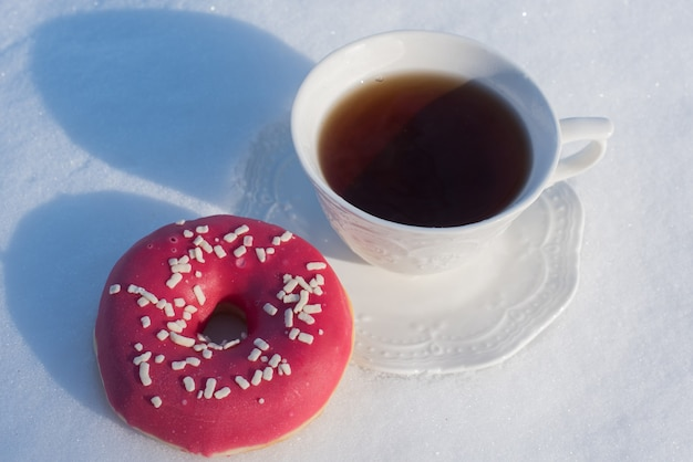 Tasse de thé pour le petit déjeuner avec des beignets sur fond de neige