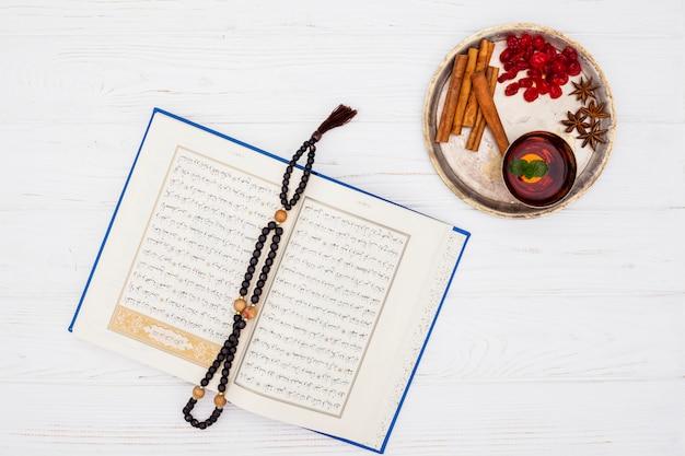 Tasse de thé près des épices sur un plateau et livre avec des perles