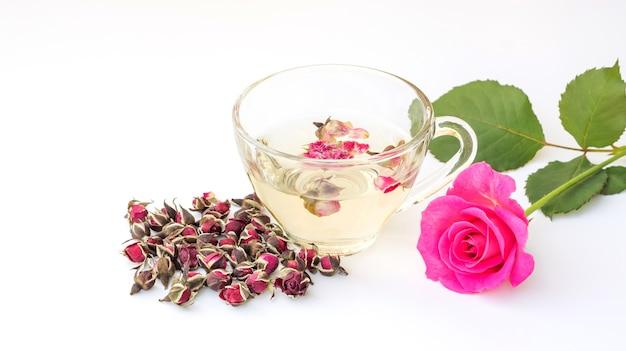 Une tasse de thé rose rose sur fond blanc.