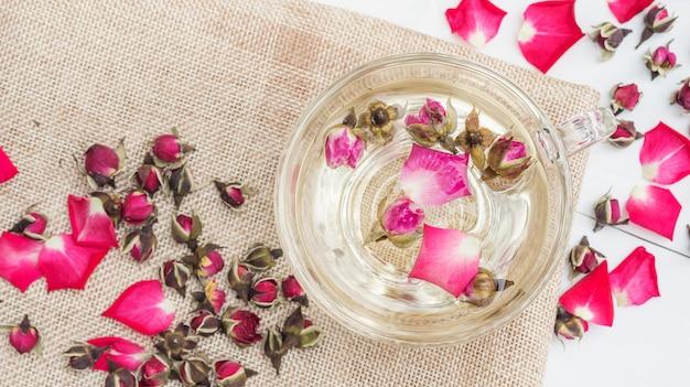 Une tasse de thé rose rose sur une table en bois blanche.