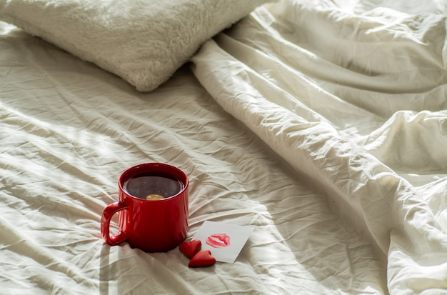 Tasse de thé rouge et biscuits deux coeurs, une note avec un baiser sur un lit blanc