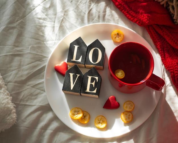 Tasse de thé rouge avec du kumquat sur l'assiette et deux coeurs cookies avec le mot love sur un lit blanc