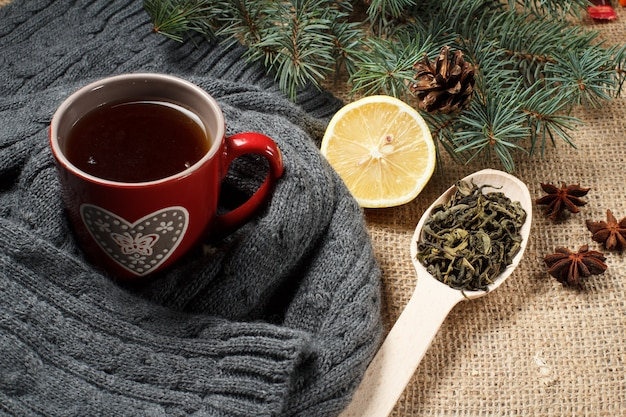 Tasse de thé rouge avec motif en forme de coeur enveloppé dans une écharpe en laine, citron tranché, cuillère en bois avec feuilles de thé vert, branches de sapin avec cône et anis étoilé sur un sac. effet tonifiant des couleurs.