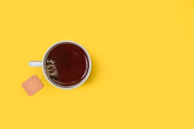 Une tasse de thé avec un sachet de thé à l'intérieur sur un fond jaune en vue de dessus avec copie espace