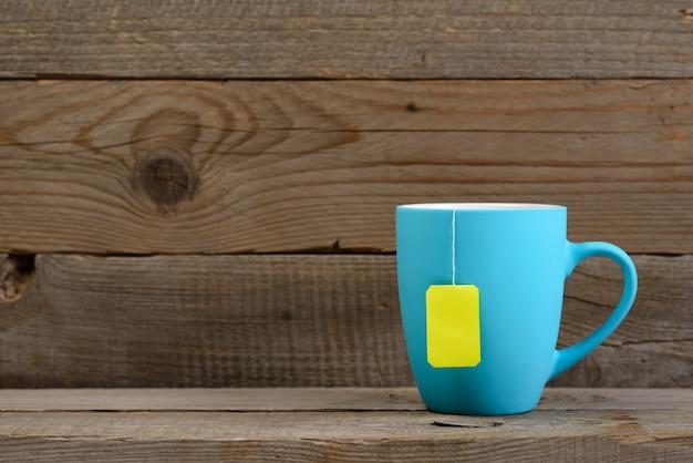 Tasse de thé avec sachet de thé sur vieux bois