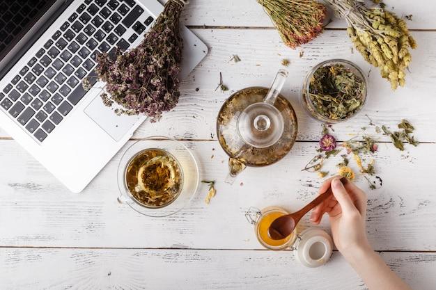 Tasse de thé sain, miel, herbes médicinales, assortiment de tisanes et baies sur table. vue de dessus. phytothérapie.