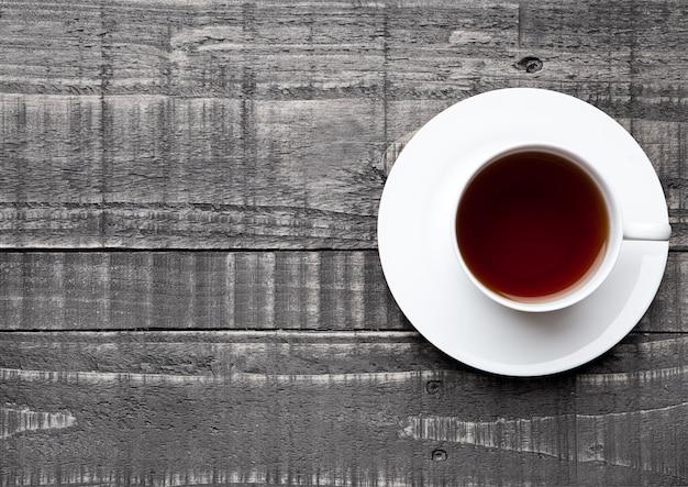 Tasse de thé sain noir sur une surface en bois