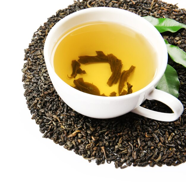 Tasse avec thé sec infusé et feuilles vertes, sur blanc