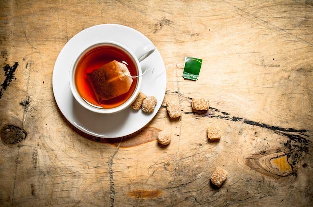 Tasse de thé et de sucre de canne sur table en bois.