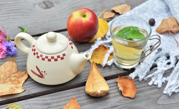 Tasse de thé sur une table en bois dans le jardin avec théière parmi les feuilles d'automne et pomme rouge sur foulard en laine