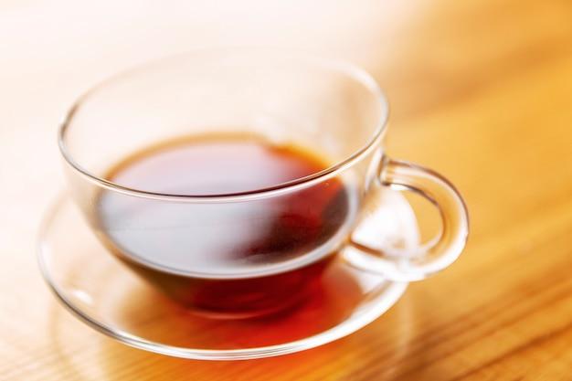 Tasse de thé sur une table en bois à la lumière du soleil. fermer.