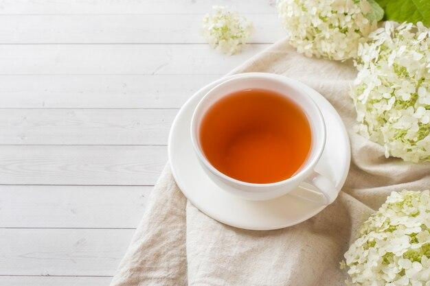 Tasse de thé sur la table avec des fleurs matin petit déjeuner