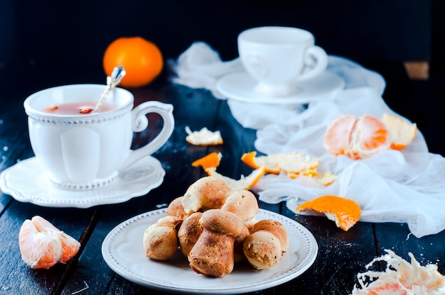 Tasse à thé avec thé et biscuits ange, mandarine sur un tableau noir