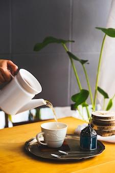 Tasse de thé avec théière et éléments de petit déjeuner