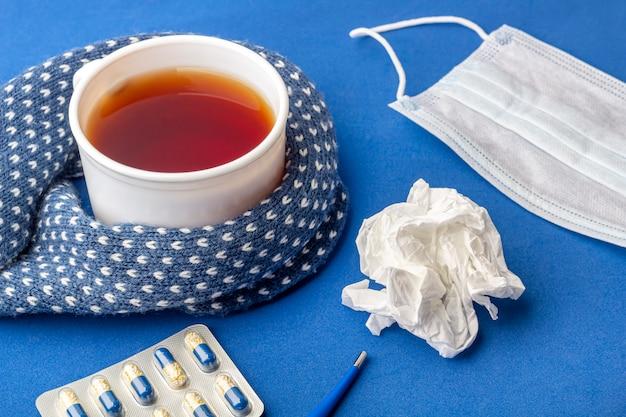 Tasse de thé, thermomètre, serviette froissée et masque médical sur bleu