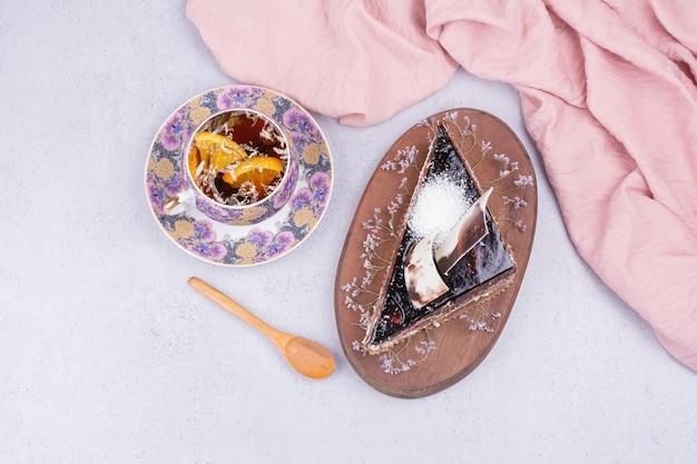 Une tasse de thé avec une tranche de gâteau au chocolat sur une surface grise