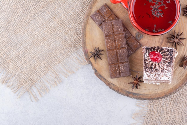 Tasse de thé, tranche de gâteau et barre de chocolat sur pièce en bois.