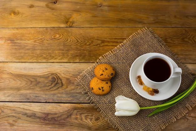 Tasse à thé et tulipes blanches sur un sac, vue de dessus, espace copie