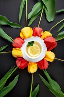Tasse de thé avec des tulipes rouges et jaunes autour.