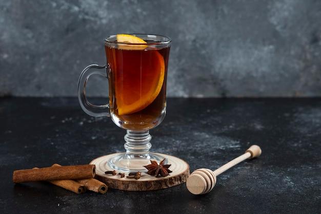 Une tasse de thé en verre et avec des bâtons de cannelle et une louche en bois.