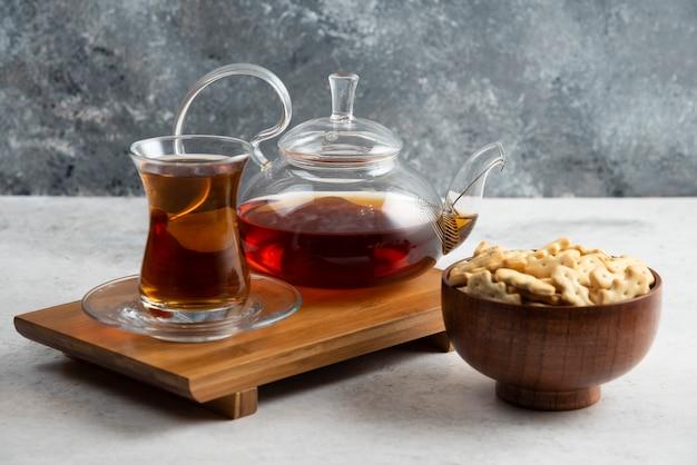 Une tasse de thé en verre avec un bol en bois plein de craquelins.