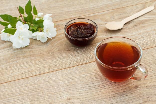 Tasse de thé en verre, confiture de fraises maison, cuillère en bois et fleurs de jasmin blanc sur fond de bois. vue de dessus.
