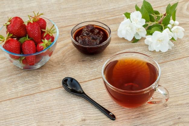 Tasse de thé en verre, confiture de fraises maison et fraises fraîches dans des bols, cuillère et fleurs de jasmin blanc sur des planches en bois.