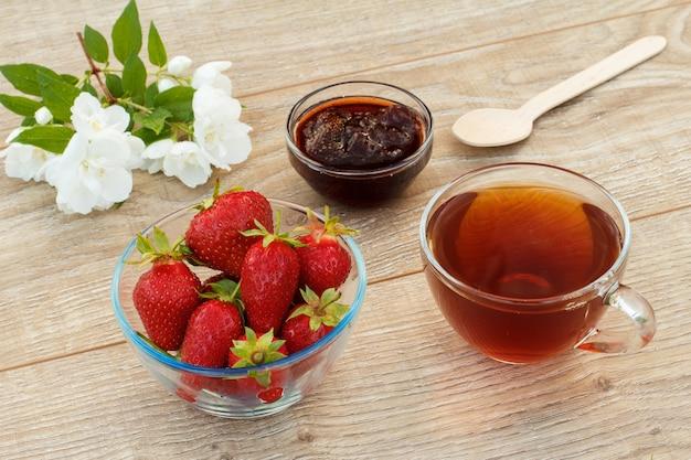 Tasse de thé en verre, confiture de fraises maison et fraises fraîches dans des bols et fleurs de jasmin blanc sur fond de bois. vue de dessus.