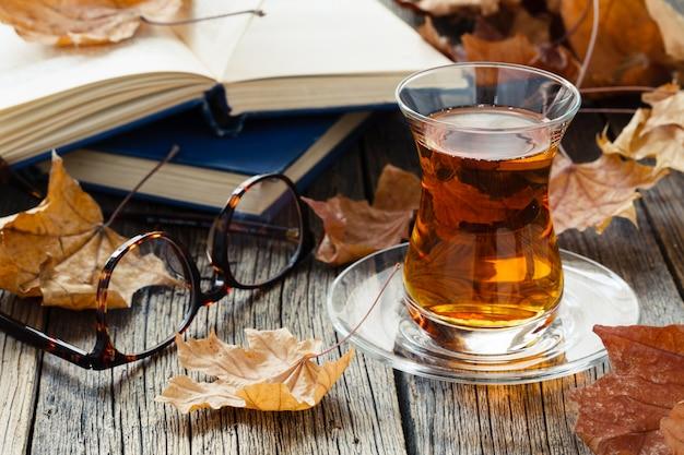 Une tasse de thé en verre dans un environnement d'automne