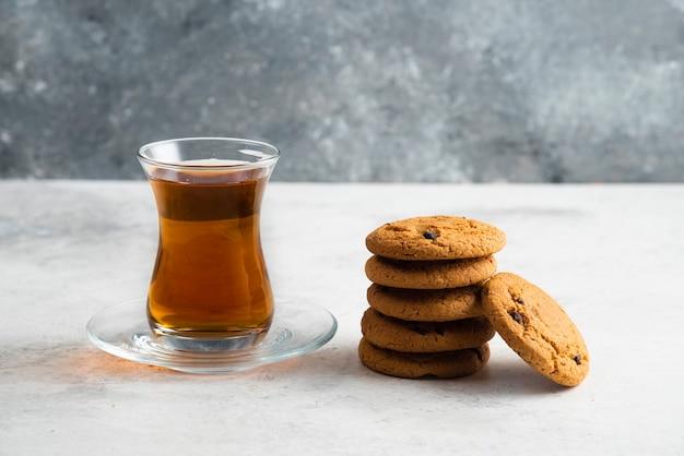 Une tasse de thé en verre avec de délicieux biscuits.