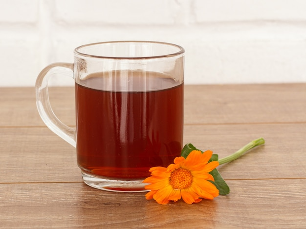 Tasse de thé en verre avec des fleurs de souci jaune sur un bureau en bois.