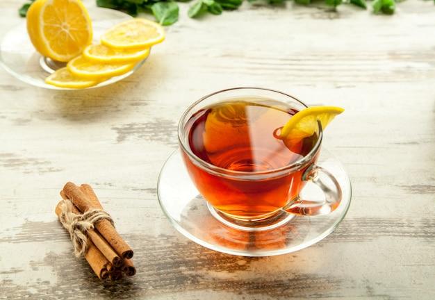 Tasse de thé en verre sur une table en bois avec des tranches de citron et de cannelle.