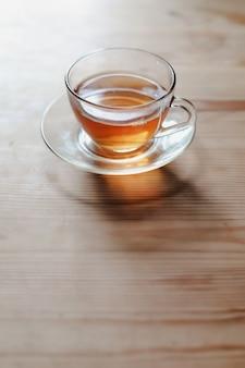 Une tasse de thé en verre sur une table en bois