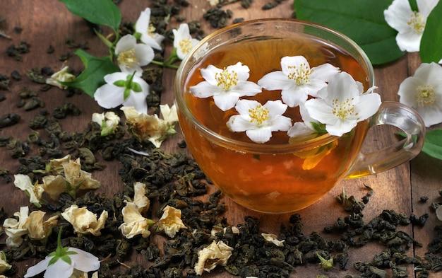 Tasse de thé vert au jasmin sur une table en bois.