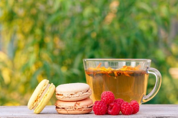 Tasse de thé vert aux fleurs de calendula, délicieux gâteaux de macarons et framboises fraîches.