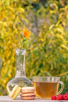 Tasse de thé vert, délicieux gâteaux de macarons, framboises fraîches et fleur de calendula dans un flacon en verre